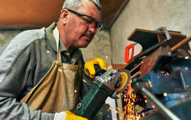 Mature worker man manufacturing in his workshop. Carpenter male grinding with sparks in repair shop.