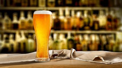 Keuken foto achterwand Bier / Cider Cold beer on desk and blurred bar interior.