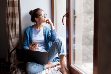 Remote working from home office. Young woman using laptop, phone. Freelancer workplace by window. Teleworking in isolation, female business, shopping online, distance education. Lifestyle moment.