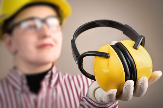 Young woman in safety glasses and helmet holds earphones in her hand for hearing protection: safety and health at work concept and protective equipment