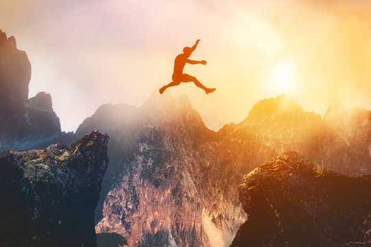 Man jumping between rocks. Overcome a problem for a better future