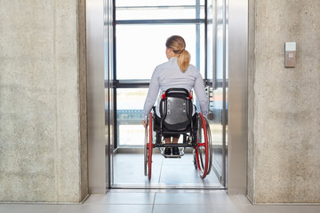 Businesswoman in a wheelchair drives with the elevator