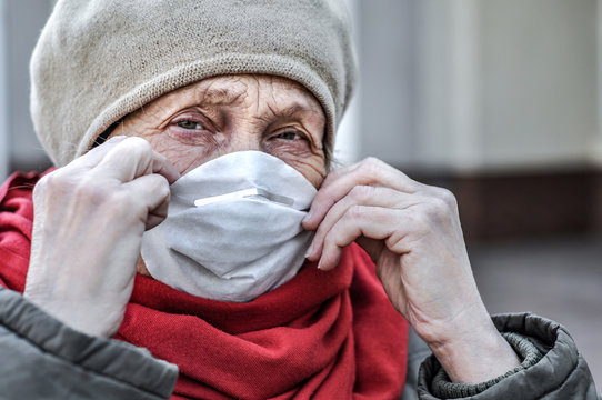 An elderly woman puts a respirator on her face - a protective mask against coronovirus infection. COVID-2019 Senior Health. The threat to the life of the elderly coronavirus