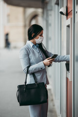 Elegant business woman with protective mask standing on city street and using ATM machine to withdraw cash. Corona or Covid-19 virus pandemic concept.