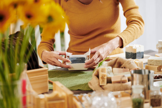 Close-up image of woman packing fragrant soap she made at home in paper box