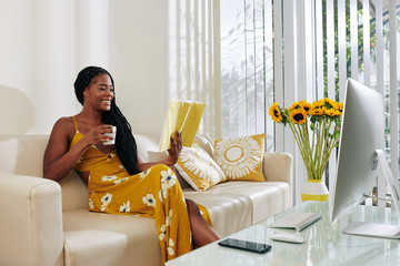 Beautiful smiling young woman drinking cup of delicious coffee and reading book when staying at...