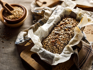 Gluten-free homemade buckwheat bread with the addition of various seeds in a baking tin on a wooden board close up
