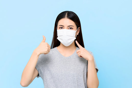 Young Asian woman wearing face mask to protect from COVID-19 and giving thumbs up isolated on light blue background