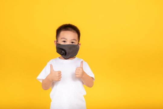 Little asian children boy wearing medical mask protection coronavirus COVID-19 or dust pm2.5 tumbs up safety healthy self air pollution concept on yellow background isolated studio shot, copy space.