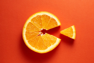 Fototapeta Orange slice symbolizing vitamin c is eating the cut out piece on orange background obraz