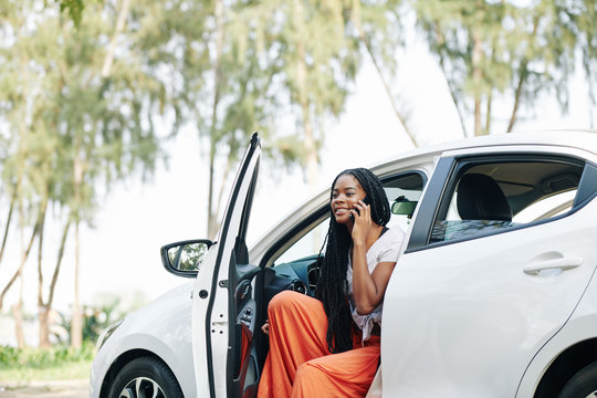 Young smiling woman talking on phone when getting out of car