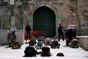 Muslim worshippers pray near a closed gate of the compound housing Al-Aqsa mosque, known to Muslims as Noble Sanctuary and to Jews as Temple Mount in Jerusalem's Old City