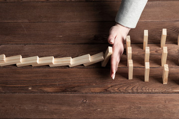 Businesswoman protecting dominoes from falling