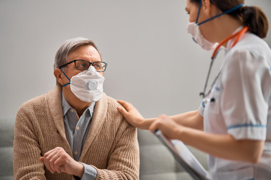 Doctor and senior man wearing facemasks