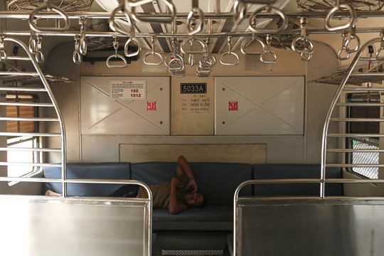 Railway employee talks on the phone inside an empty train compartment in Mumbai