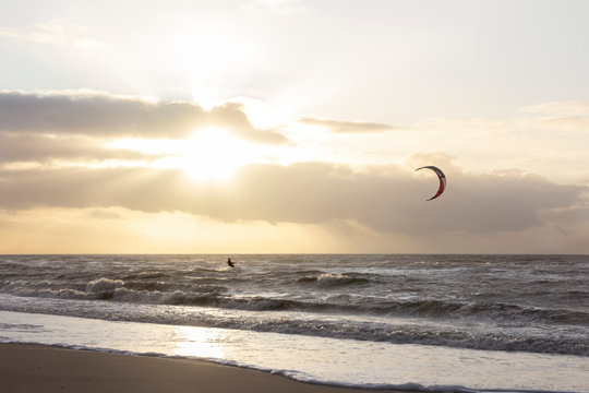 View of the north sea beach on a windy winter day at sunset, people, kitesurfing. Noordwijk, the Netherlands