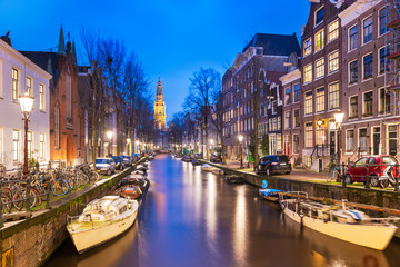 Fotomurales - Amsterdam, Netherlands canals and church tower at dusk.