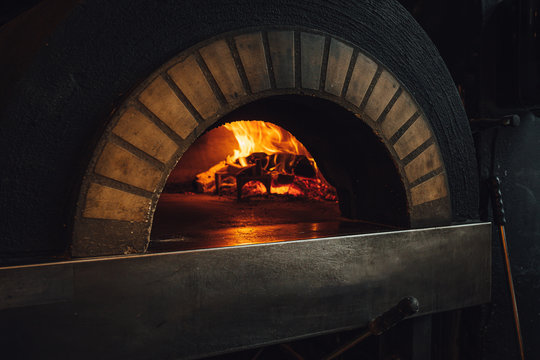 Dark brick pizza oven with fire in restaurant