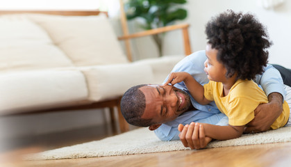 Happy African Father and little child son spending time playing at home together. Smiling Dad in blue shirt embracing or cuddling kid boy in yellow casual after arriving from working on wooden floor.