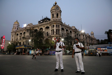 A police officer uses a megaphone advising people to vacate the roads after the lockdown by West Bengal state government to limit the spreading of coronavirus disease (COVID-19), in Kolkata