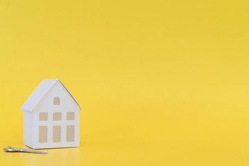 close up model's home  and key on yellow color background with space for money management ,home loan refinance and personal financial concept
