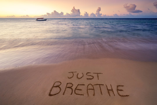 handwritten Just breathe on sandy beach