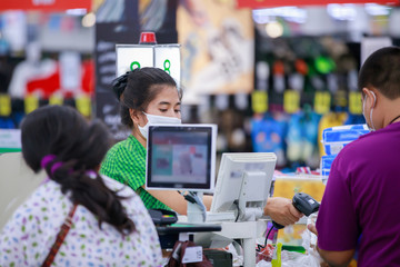 People buying goods in a grocery store.Cashier or supermarket staff and customers in medical protective mask