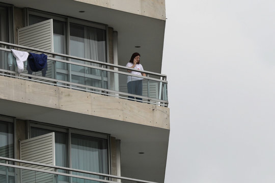 A woman, who flew back from Spain, is seen on the balcony of a hotel where she was placed in a two-week quarantine, after the Greek government imposed a nationwide lockdown to contain the spread of the coronavirus disease (COVID-19), in Athens