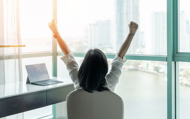 Business achievement concept with happy businesswoman relaxing in office or hotel room, resting and raising fists with ambition looking forward to city building urban scene through glass window Fotomurales
