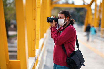 A photographer journalist shoot to reckless people on crowded street with a mask in a quarantine period because of pandemic global danger. Fotobehang
