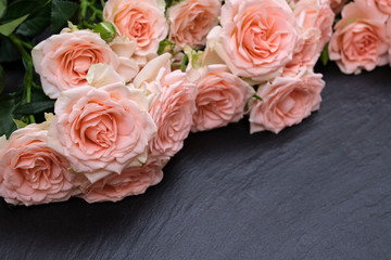 Foto op Canvas Lelie Fresh pink roses on a black background made of natural stone. Copy space
