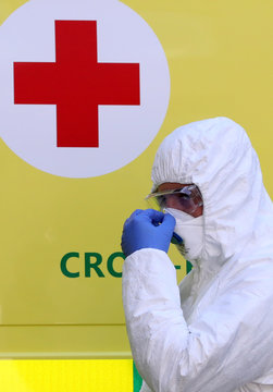 A member of medical staff walks in front of the Red Cross logo at CHC Montlegia hospital in Liege