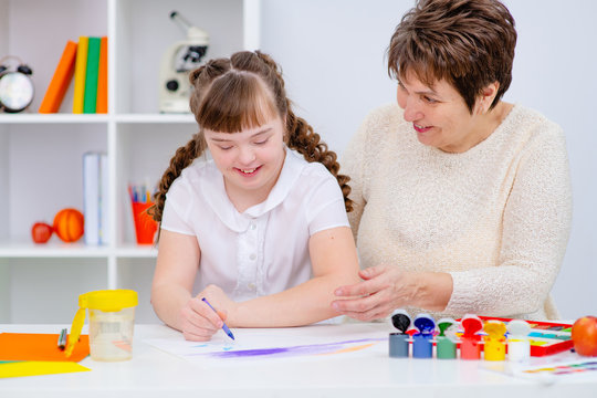 Mom deals with a girl with Down syndrome. The concept of home schooling and classes. Mother and daughter play together