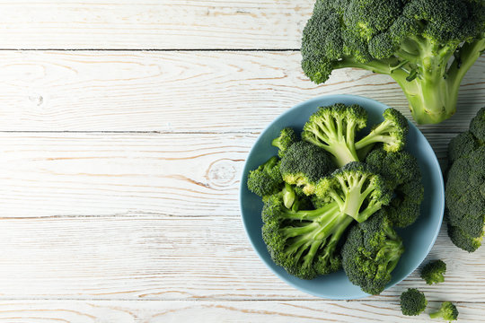 Plate with broccoli on wooden background, top view. Healthy food