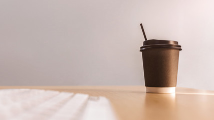 take away paper cup of hot coffee with computer keyboard on top of wooden working table in morning sunlight