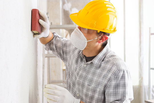 Plasterer or painter sanding a white wall