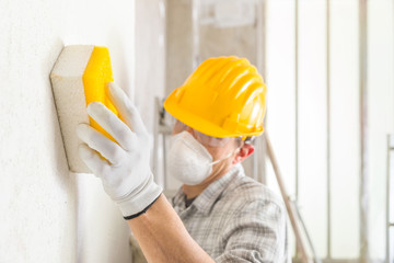 Plasterer or building sanding and smoothing a wall