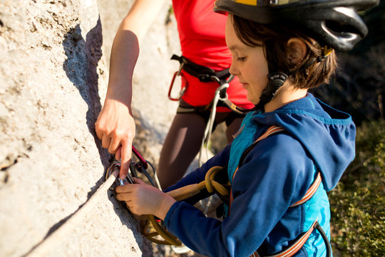 The instructor teaches the child to use safety equipment.