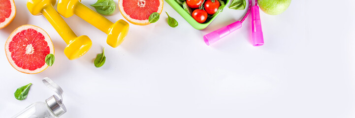 Fitness and healthy food lifestyle concept. Dumbbells, diet fruit and vegetable lunch box, water and jump rope on white background. Flatlay image, top view copy space