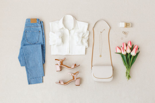 Blue jeans, white shirt, heeled sandals,  small cross body bag with chain strap, pink tulips on beige background. Woman's stylish spring summer outfit. Trendy women's clothes. Flat lay, top view.