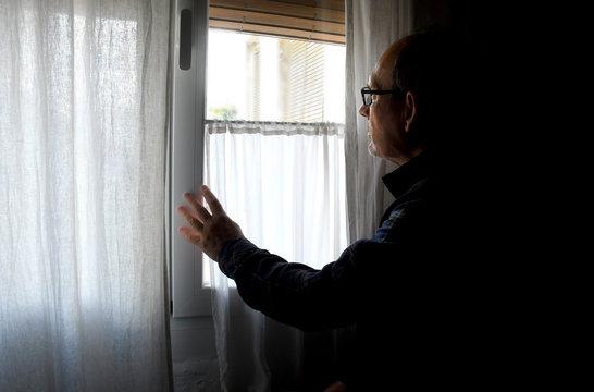 Un hombre mayor, confinado por la cuarentena del COVID-19, mira a través de la ventana de su casa