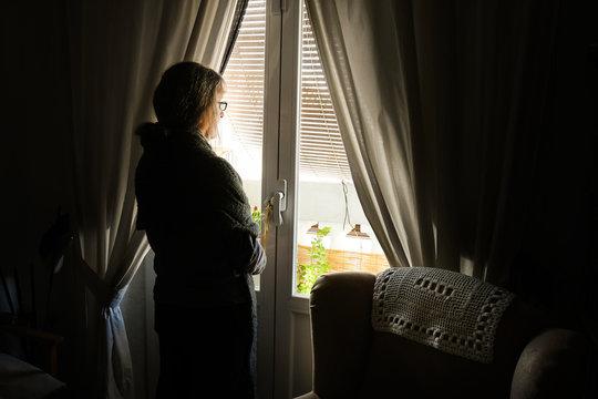Mujer adulta, confinada por la pandemia del coronavirus COVID-19, mira hacia la calle a través de la ventana de su casa
