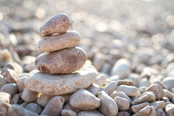 Photo sur Plexiglas Zen pierres a sable Zen pyramid from spa stones on a blurred sea background. Sea stones on the coast. Sea coast. Place for text. Sea view. A stone structure on the beach