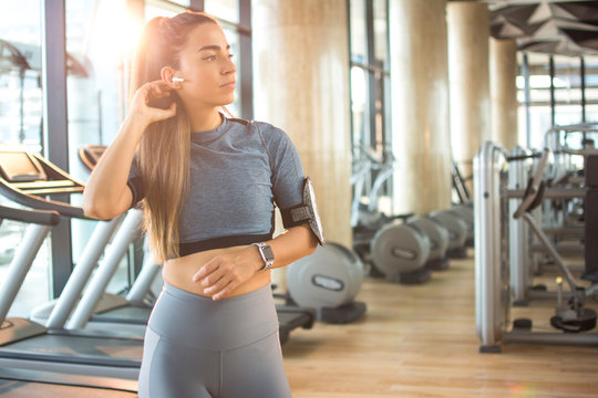 Beautiful young woman in sportswear with airpods listening to music in gym