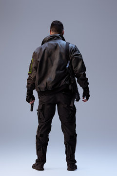 back view of cyberpunk player holding gun and standing on grey