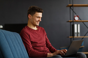 Young freelancer working in home with laptop. Texting messages, browsing internet. Studying online, online education, remote working. Young people working at home. Business concept.