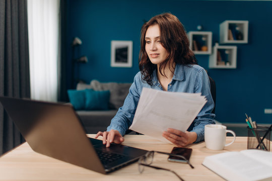 Confident young lady with curly hair working on laptop and reading paper documents at home. Cheerful woman in denim shirt sitting at table and using computer.