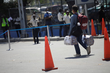 A man carries luggage as he walks at International Airport Toussaint Louverture, after Haiti's government declared a state of emergency over the coronavirus disease (COVID-19) outbreak, in Port-au-Prince