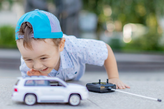 a small boy plays with a toy car on radio control holding a remote control