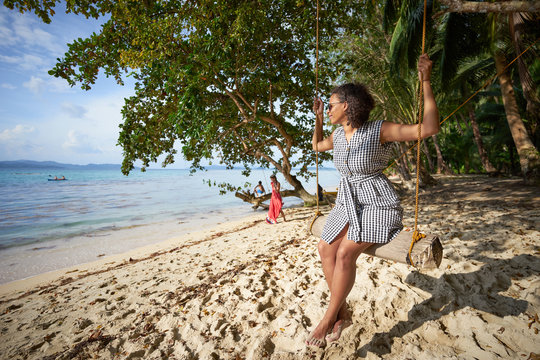 """Attractive black woman on a swing at the """"White Beach"""", Port Barton, Palawan, Philippines"""